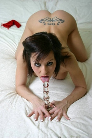 Naked brunette Kream masturbates with a glass dildo on a bed in high heels