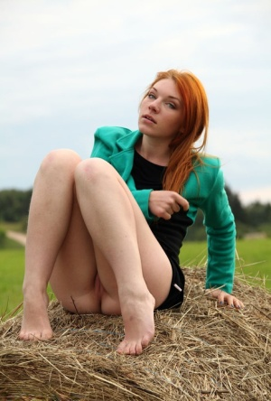 Natural redhead Amber A poses her naked teen body on round bale of hay