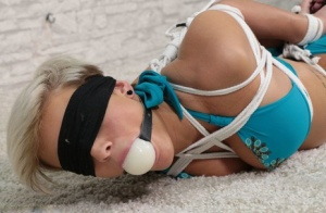 Short haired girl is ballgagged and hogtied in bare feet and a bikini