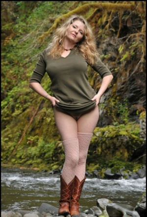 Mature blonde releases her big tits as she strips to cowgirl boots by a stream