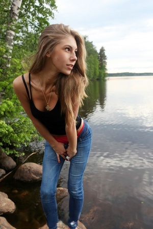 Girl next door Megan pulls out her tits while sitting on a rock in the lake