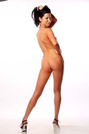 Naked amateur with long legs piles hair on head while striking sexy poses