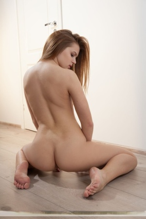 Sexy redhead Nika K showcases her shaved vagina while modeling naked