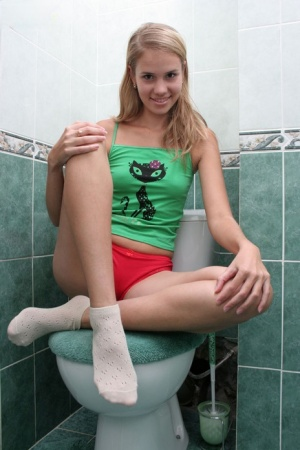 Young blonde strips to her white socks on top of a toilet seat