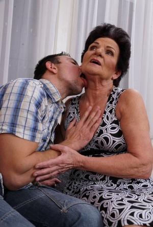 Old woman kisses her toy boy before the undress each other on sofa