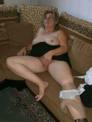 Old woman with large boobs pulls down pantyhose to finger her natural pussy