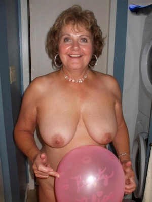 Naked mature woman Busty Bliss gets into a bathtub filled with balloons