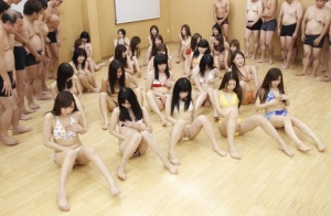 Japanese swingers gather for a group sex session on hardwood flooring