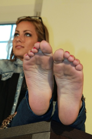 Solo model Valeria removes flat shoes from bare feet while fully clothed