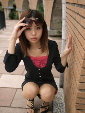 Fully clothed Japanese girl lifts up sunglasses to show her pretty face