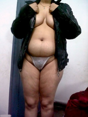 Fat Indian woman hides her face while adorned in a bra and thong