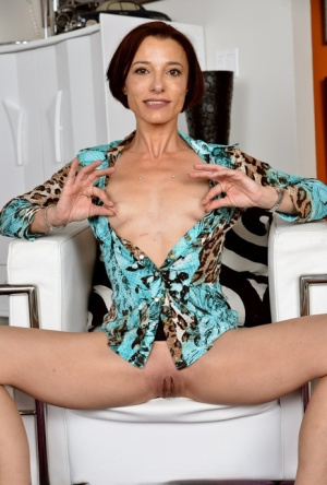 Thin mature housewife Stella Banks grabs her ass while modeling in the nude