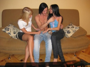 Young looking girls and their man friend have a threesome on a couch