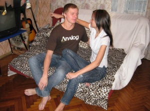 Young brunette and her boyfriend doff T-shirts and jeans before sex on a bed
