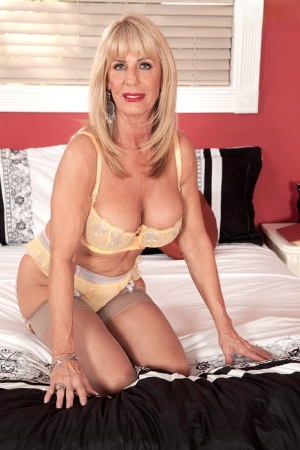 Old mature blonde frees her big hot boobs to give her young boy toy a blowjob
