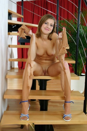 Sweet teen girl removes her tan pantyhose to finish getting undressed
