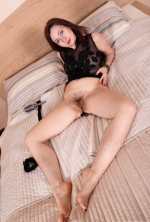 Hairy woman Vita removes her onesie and stockings on top of bed