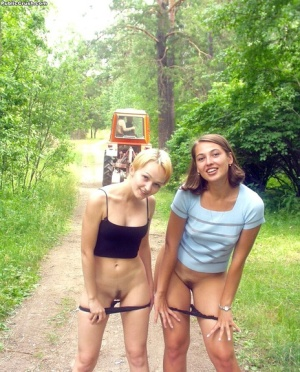 Teen lesbians exposes themselves and lick nipples while on a path in the woods