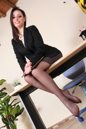 Brunette secretary Ilaria removes black pumps in a skirt and pantyhose