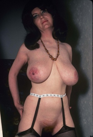 Vintage chick with big hair and big boobs sucks her own nipples