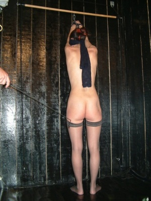 Female slave is blindfolded before being flogged and caned in stockings