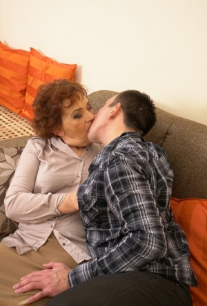 Old redhead and her toy boy engage in foreplay before getting down to fuck