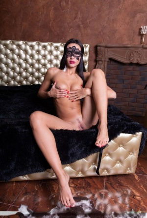 Sexy brunette Leyla Lee removes a mask and robes to pose nude with a feather