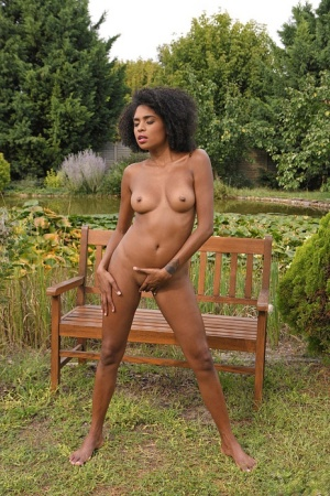 Black girl Luna Corazon spreads her pussy after getting naked on garden bench