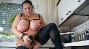 Mature BBW unleashes her massive boobs before toying her pussy in the kitchen