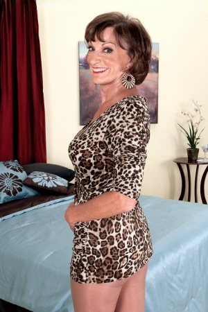 Mature granny removes her short dress to pose in sheer pantyhose and boots