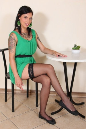 Clothed girl Dollyc frees stocking covered feet from flat shoes at a table
