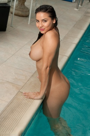 Naked brunette Lacey Banghard poses for a solo shoot while in a swimming pool