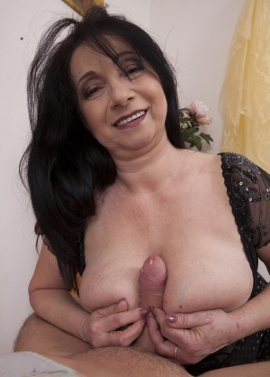 Big titted cougar Deb titty fucks and jerks on a hard cock