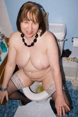 Mature woman Dirty Doctor takes a piss in a toilet before posing nude in boots