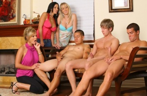 3 clothed MILFs strips a couple of boys naked and suck their cocks