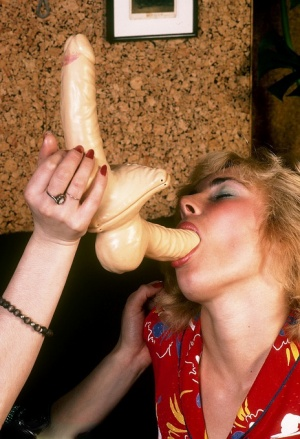 Lesbian women in retro nylons and garters share a double ended dildo