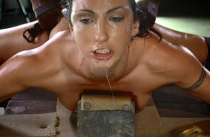 Restrained brunette is used as a cum receptacle on wooden cross