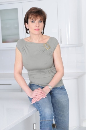 Mature wife Lady Sonia flaunts big tits braless in t-shirt in the kitchen