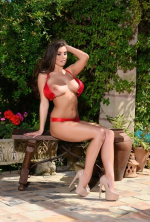 Gorgeous brunette Sarah Mcdonald uncovers her big tits on a bench on the patio