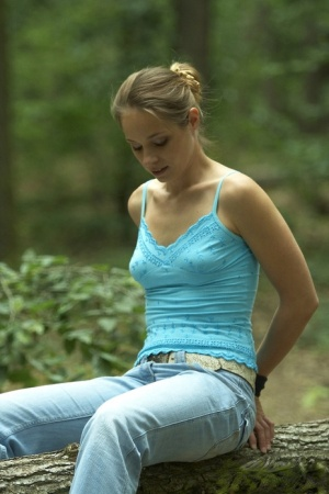 Skinny blonde girl is ties to a freshly cut tree in the forest