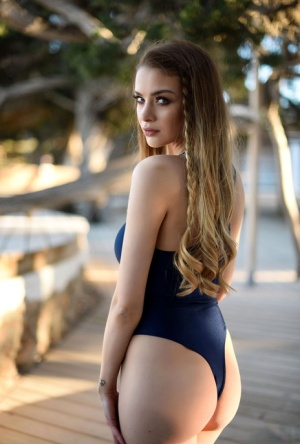 Euro chick Emelia Paige lets her big tits loose from swimsuit on the boardwalk