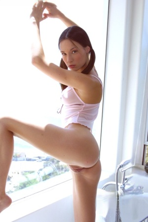 Slender young Elle in pigtails flashing small tits and tiny ass in the window