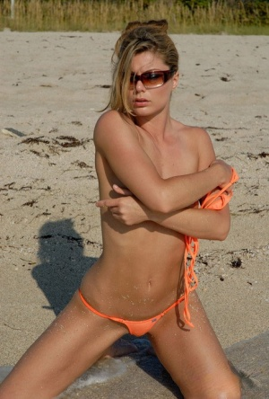 Hot beach beauty Amber in skimpy bikini poses on her knees in the sand 24047228