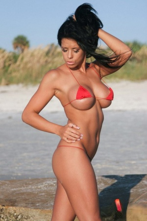 Solo model with jet black hair flaunts her clothed body in tiniest of bikinis