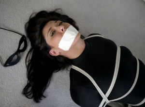 Clothed woman Tomiko is silenced with tape over mouth while tied up with rope 64144660