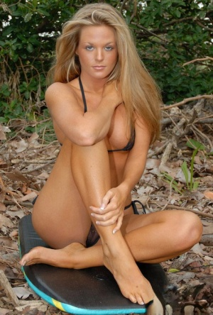 Natural blonde model with long hair removes her bikini top in the forest 74676606
