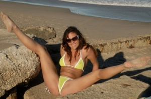 Solo girl models with her legs wide open in a bikini on the beach at the ocean
