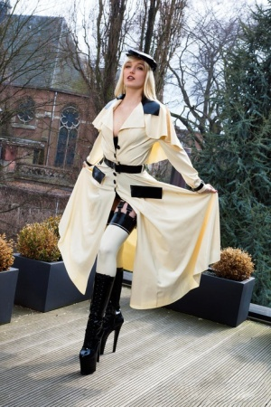 Classy blonde flashes the village below on her patio in latex attire