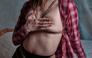Caucasian girl in a checked shirt and opaque pantyhose is tied up with rope