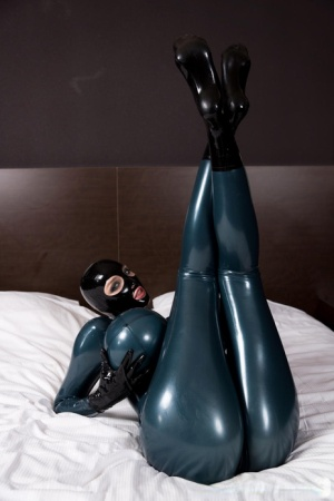 Clothed female models on bed with curtains open in rubber bodysuit and hood 33386373